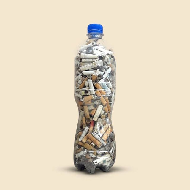 A clear plastic bottle filled with cigarette butts