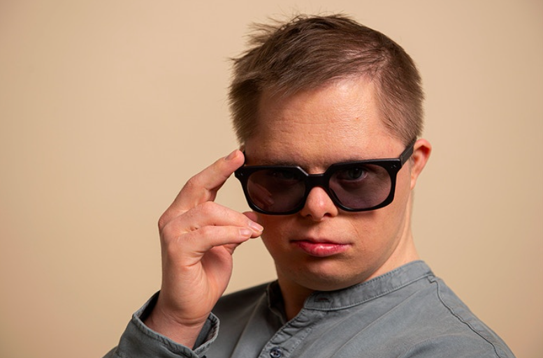 A man with Down syndrome sporting a pair of black sunglasses